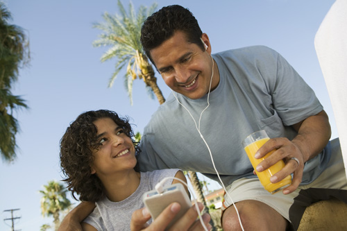 Boy (13-15) holding portable music player, father listening with earphones and holding glass of juice.