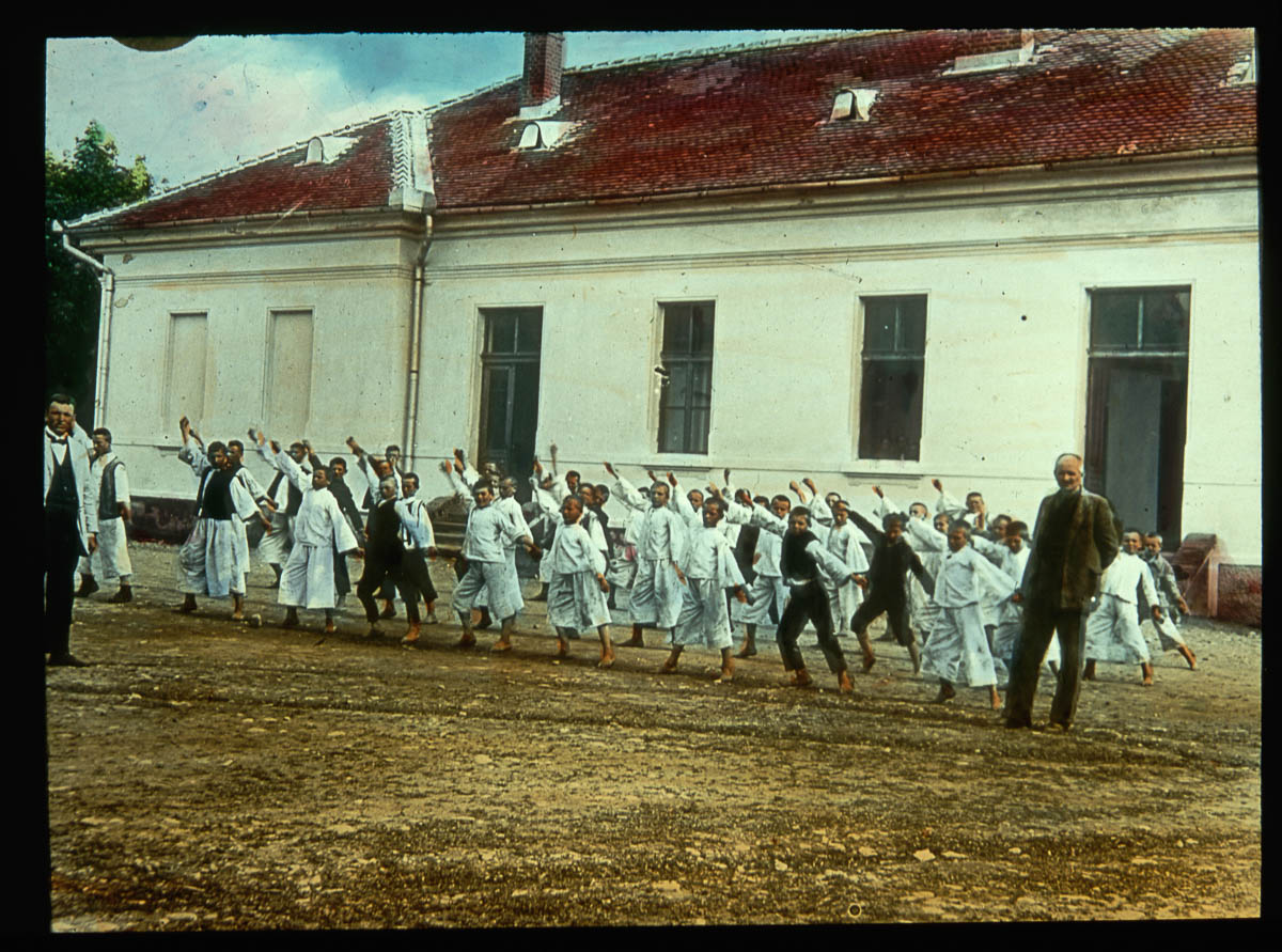 Student wearing uniforms line up and perform exercises in their physical education class. Their school is in the background.Subcarpathian Ruthenia, Czechoslovakia. | Location: Subcarpathian Ruthenia, Czechoslovakia. (Photo by Jar. Novotny/Scheufler Collection/Corbis/VCG via Getty Images)