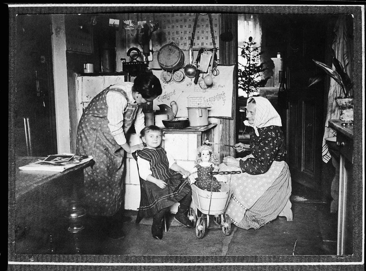 Two women and a girl by a coal stove in a Prague kitchen. The girl sits beside a doll in a pram. (Photo by Jan Honzak/Scheufler Collection/Corbis/VCG via Getty Images)
