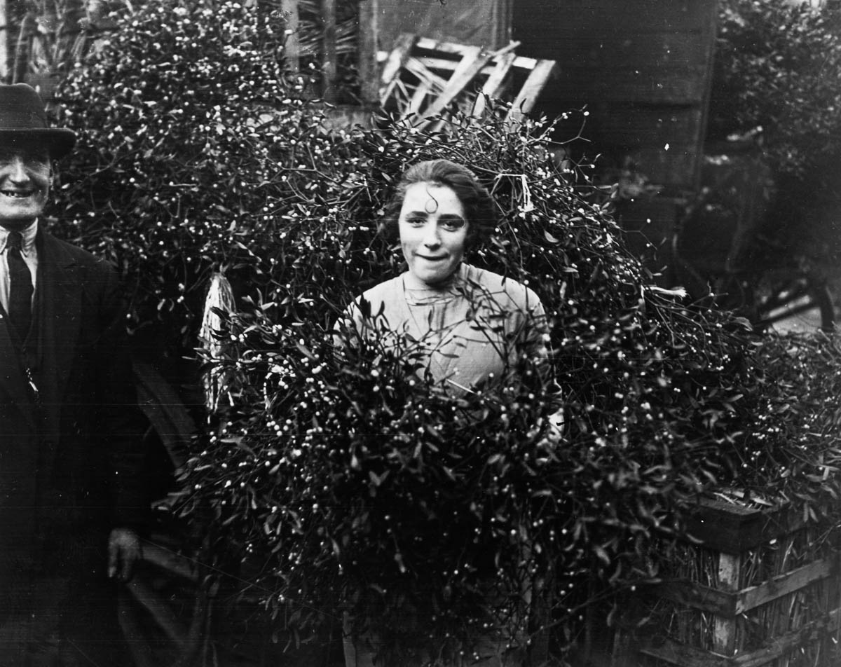 17th December 1928: A couple standing amongst the first delivery of mistletoe at Covent Garden market, London. (Photo by H. F. Davis/Topical Press Agency/Getty Images)
