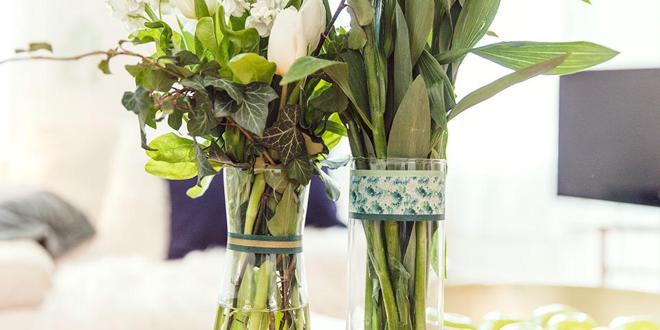 Detail vázy s dekoračními papírovými páskami v zelené